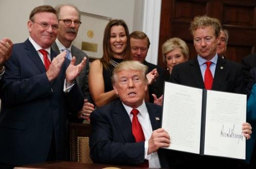 当地时间12日,在与可能受益的小企业主在白宫会面时,特朗普举起了他签署的医保行政命令。(图片来源:美联社)