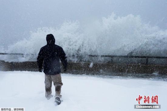 波士頓郊區市民站在海堤邊觀看波濤奔湧上岸。