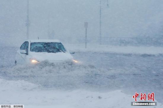 """當地時間2018年1月4日,美國麻薩諸塞州波士頓郊區遭暴風雪襲擊,海水湧上防波堤將道路變成""""冰河""""。圖為波士頓郊區風雪漫天,汽車行駛在積水中。"""