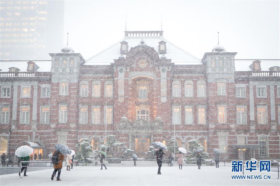 1月22日,在日本東京,行人在日本鐵路公司東京站前冒雪行走。